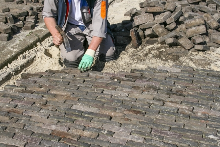 pave: Bricklayer paving a street in the Netherlands