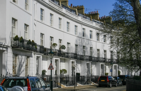 Row of Georgian terraced houses in London with parked cars in front