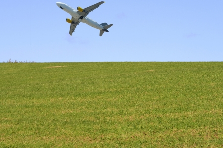 Airplane taking off in a blue sky above green grass photo