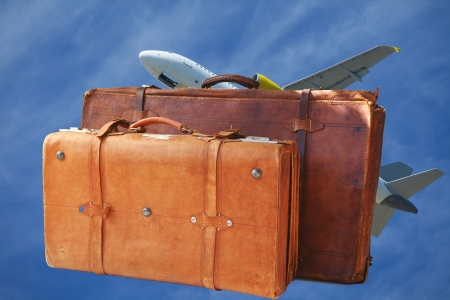 lets: Two leather suitcases with an airplane against a blue sky Stock Photo