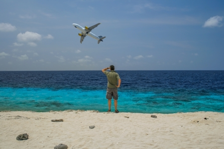 missed: Man on caribbean beach looking at aircraft rising up in the air over a blue ocean