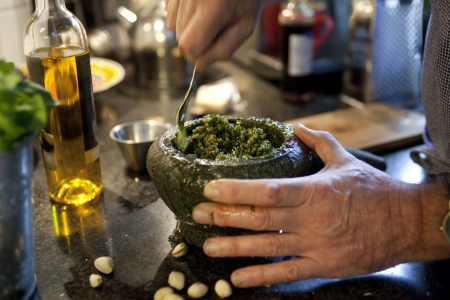 Man mixing pesto in mortar in kitchen photo