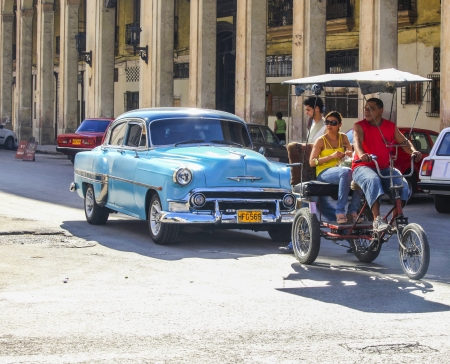 HAVANA-Feb 2: A taxi-bike and a vintage car in a street in Havana, Cuba on Feb 2, 2011 . Oldsmobiles and taxi bikes are the normal way of transport as new cars are too expensive are impossible to import by ordinary Cubans