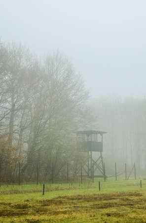 detention: HOOGHALEN, NETHERLANDS -NOV 24: Watchtower in the mist on  former concentration camp Westerbork on Nov 24, 2012 in Hooghalen, Netherlands. Westerbork was a World War II Nazi refugee, detention and transit camp.