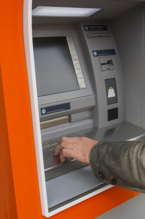 Man at ATM or cash dispenser and  entering PIN; only hand to be seen photo