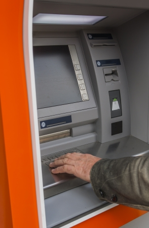 cashpoint: Man at ATM or cash dispenser and  entering PIN; only hand to be seen Stock Photo