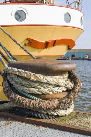 marine industry: dock with ropes and old ship Stock Photo