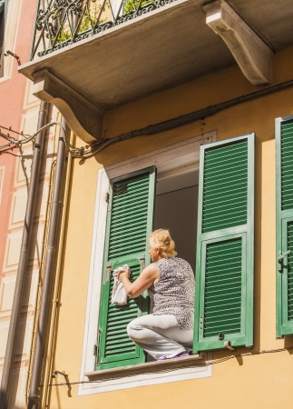 PARMA, ITALY-APRIL 15: Woman cleaning shutters sitting in open window on third floor in Parma on April 15, Italy. Window cleaning is considered one of the the most dangerous jobs. Several window cleaners die each year, and many are injured.