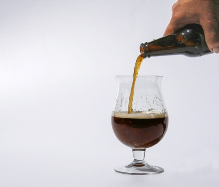 Male hand pouring dark beer in glass photo
