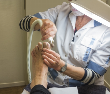 correction: GRONINGEN, NETHERLANDS-APRIL 24: Pedicurist treating foot of woman in salon. (Medical) pedicure is important for elderly. After 75, fewer than 30% of patients can still look after their feet themselves because they can't see well, they can't reach the