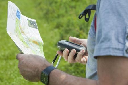 男は彼の手で GPS 受信機とプランを保持しています。ハンドヘルド GPS デバイスのウォーキングやハイキング屋外レジャー産業で主に使用されます。