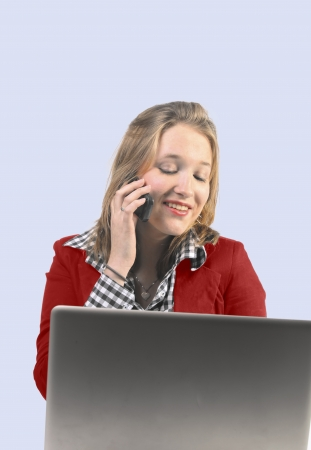 Young woman with red jacket answering phone while looking at laptop photo