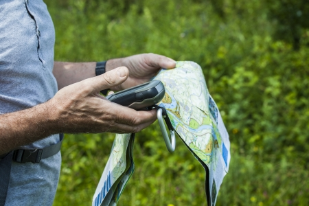 predominantly: Man holding a GPS receiver and plan in his hand in a green environment  Handheld GPS devices are used predominantly in the outdoor leisure industry for walking and hiking  Stock Photo