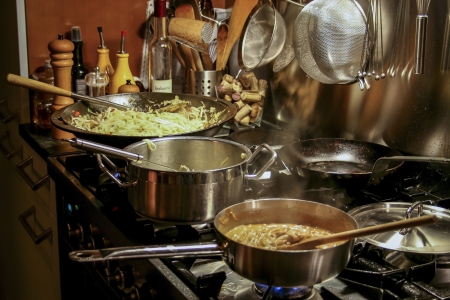 stirring: Asian meal with noodles and peanut sauce cooked on a stove