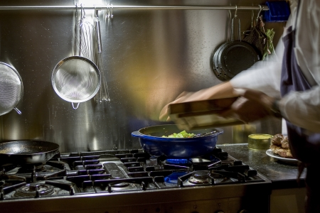 making a fire: Man is cooking at big stove  Stock Photo