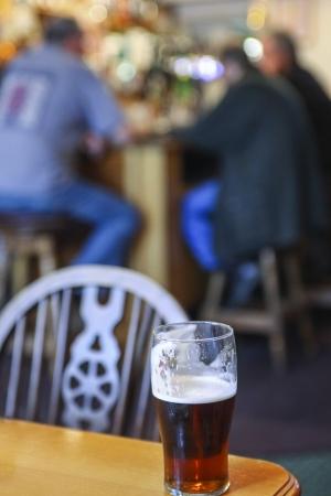 cerveza negra: Vidrio con cerveza negra sobre la mesa en un pub escoc�s Foto de archivo