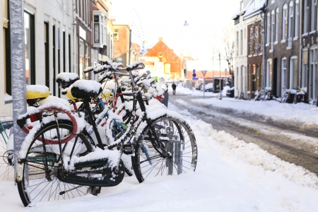 rust covered: Row of bikes in the snow in Dutch Groningen Stock Photo