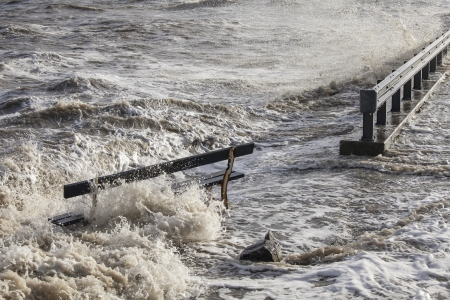 torrential: Waves of ocean water surrounding a wooden bench after heavy rains and storm in a coastal town in the Netherlands