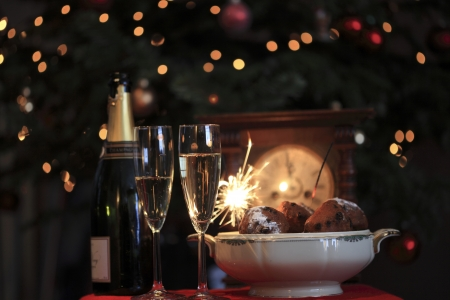Happy new year! New year design of a typical new Years eve in the netherlands with champagne, sparkles and oliebollen Stock Photo