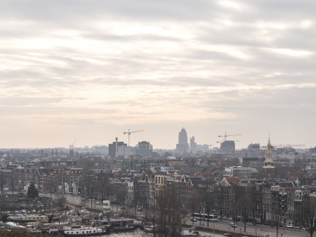AMSTERDAM, NETHERLANDS - JAN 18,2014: Historic buildings in the center of Amsterdam and new and modern buildings at the horizon. The country's largest city is visited by over 3,5 million foreign tourists a year.