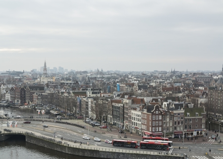 AMSTERDAM, NETHERLANDS - JAN 18,2014: Historic buildings and busses in the center of Amsterdam. The countrys largest city is visited by over 3,5 million foreign tourists a year.