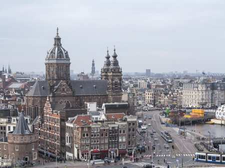 AMSTERDAM, NETHERLANDS - JAN 18,2014: Historic buildings with the famous St. Nicolaaschurch  in the center of Amsterdam. The countrys largest city is visited by over 3,5 million foreign tourists a year.