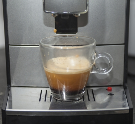 espresso machine: Coffee machine with glass of black coffee. Last drop of coffee is falling   Stock Photo