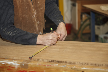 build buzz: A Carpenter is measuring the right length of a wooden board