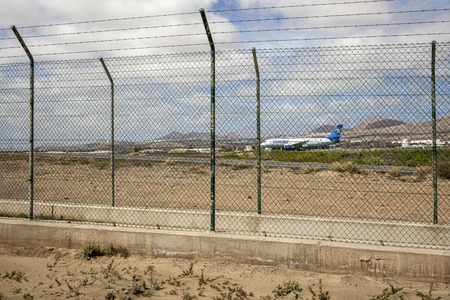 glass fence: LANZAROTE, SPAIN-FEB 6, 2013: Condor airplane waiting for take off at Lanzarote airport