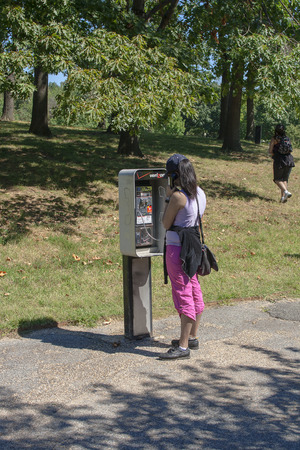 payphone: WASH DC,USA-SEPT 1: Young woman making a phone call at a public phone booth on sept 1, 2008. Pay phones are rapidly disappearing on the US streets. In 1995 there were 2.2 million in 2013 less than 500.000