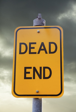 front end: Yellow road warning sign against a dark sky: Dead End