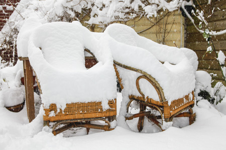 Two rotan garden chairs heavily covered with snow Stock Photo