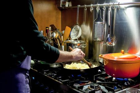 stirring: Man stirring food in pan in kitchen Stock Photo