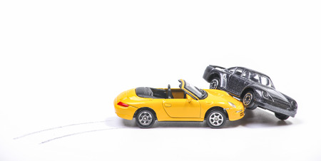 Car crash between a yellow sportscar and a black sedan with brake tracks. Simulation with model cars Standard-Bild