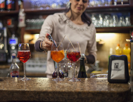 VENICE, ITALY -MARCH 12: Woman making glasses of Aperol Spritz  at a bar in Venice, Italy on March 12, 2014.Aperol Spritz is also known as Veneziano.