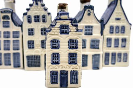 delftware: Una fila di Delft blu alias olandese case in ceramica china di cui una � in piedi fuori Parte di una serie di case blu Delft Archivio Fotografico