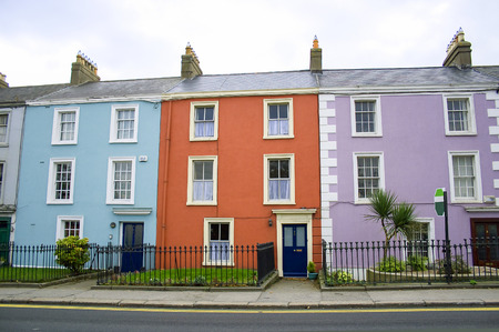row of houses: three victorian houses in orange, blue and lilac colors on a row on a Dublin street