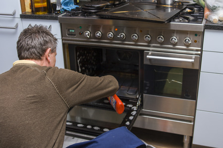 dirty man: A man kneeling on the kitchen floor and cleaning the inside of an oven.   Stock Photo
