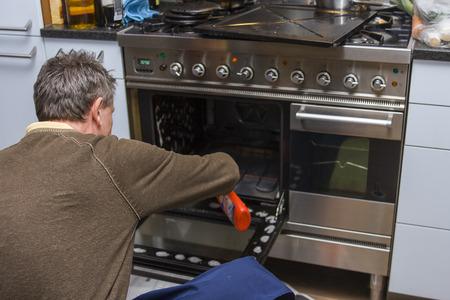 clean home: Een man knielend op de keukenvloer en het reinigen van de binnenkant van een oven.