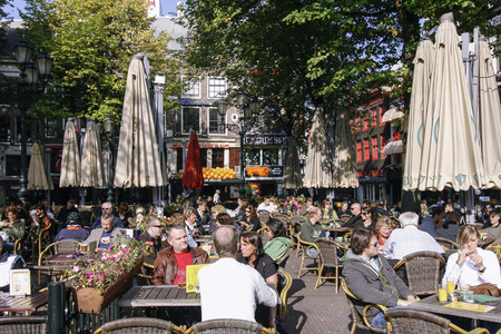 AMSTERDAM, NETHERLANDS-OCT 11: People enjoying a sunny day on the Leidseplein in Amsterdam on Oct 11, 2008. The Leidseplein is famous for its terrace especially with tourists