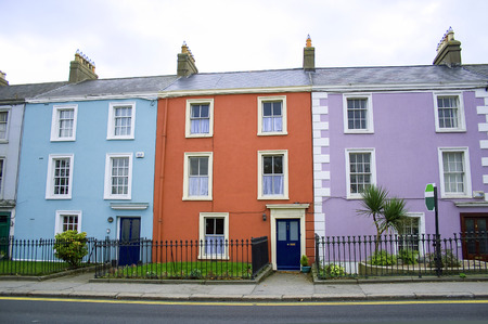 three victorian houses in orange, blue and lilac colors on a row on a Dublin street