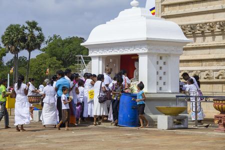 dagoba: ANURADHAPURA, SRI LANKA - AUG 10: Pilgrims praying on the main yard near the white sacred stupa Ruwanmalisaya dagoba on Aug 10, 2013 in Anuradhapura, Sri Lanka