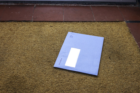 Blue envelope from the Dutch tax office on the door mat Фото со стока