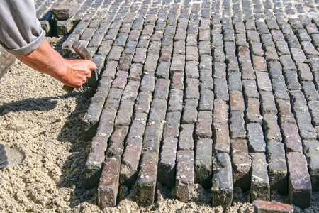 repairer: bricklayer is repairing a brick road with a brick hammer