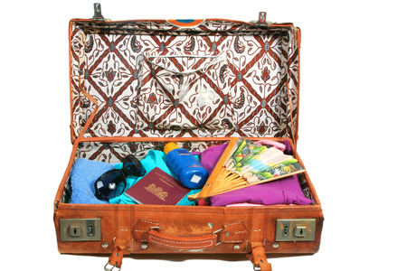 Vintage open suitcase with clothes and summer and beach items   photo