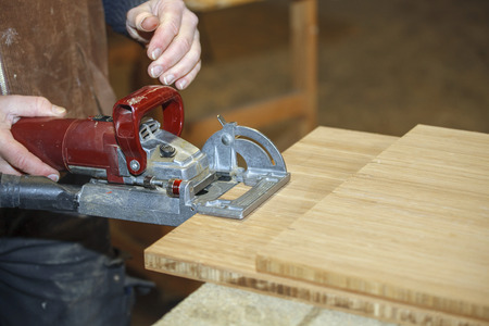 joiner: Close up of a carpenters hand working a machine in the workshop