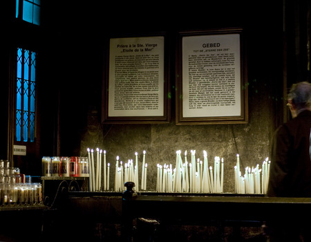 Lighted candles with written prayers in medieval church in the Netherlands Editorial