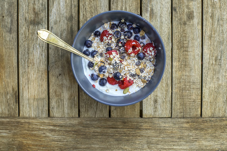 Yogurt with muesli and fresh blueberries, raspberries, sunflower seeds in bowl over old wooden background.     photo