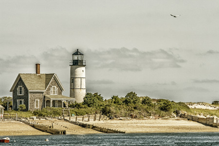 lighthouse keeper: Wooden house and white lighthouse at Cape Cod near Portland
