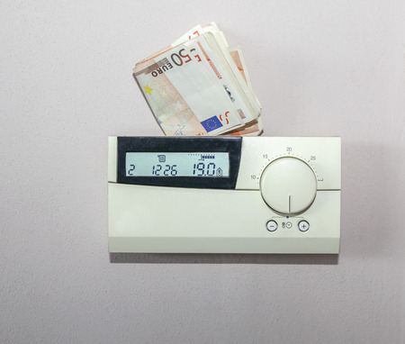 pricey: Euro bills behind the thermostat of the central heating system. Concept for the costs of energy Stock Photo